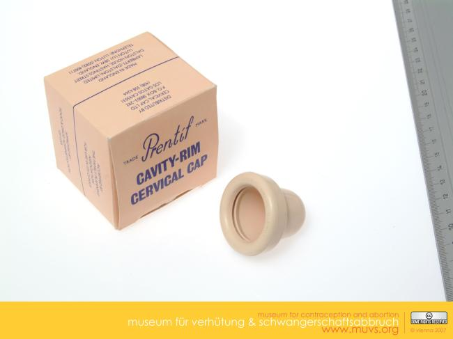 Photograph of the Prentif Cavity Rim Cervical Cap, with packaging. Ruler alongside shows rough size. The cap is beige, teat shaped, hollow, about 3 cm long, rim about the same diameter. Box is beige, square, with branding, blue writing. The Prentif Cavity Rim Cervical Cap was one of the cap types that the FDA approved in 1988 for American women's use. Courtesy of the Museum of Contraception and Abortion, Vienna, Austria (MUVS, Wien).