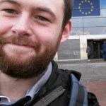 Head and shoulder view of Gareth Smith standing in front of building with EU flag over door. Gareth has a beard and is smiling. He is wearing a jacket and backpack