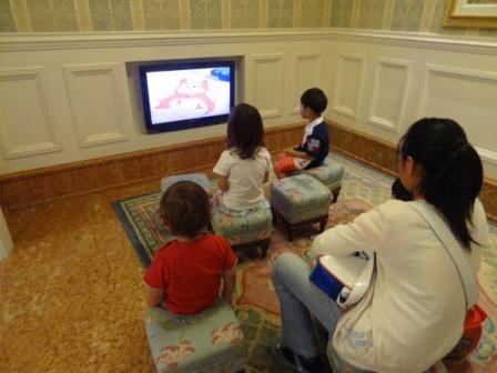 Kids watching TV  while checking in at Disneyland Hotel