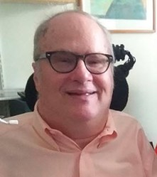 Head and shoulders photo of smiling short haired white man with dark-rimmed glasses wearing a peach colored shirt, with wheelchair headrest and sip-and-puff operating switch visible in the frame.