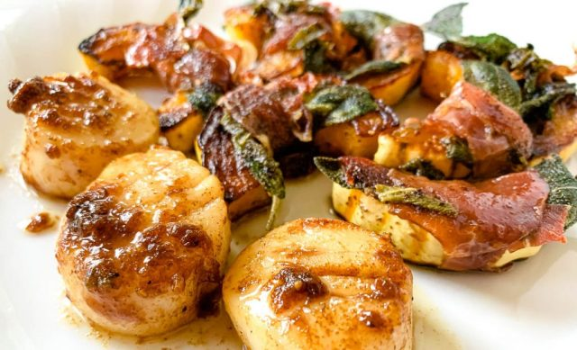 dinner scallops seared in a hot pan with squash prepared saltimbocca style