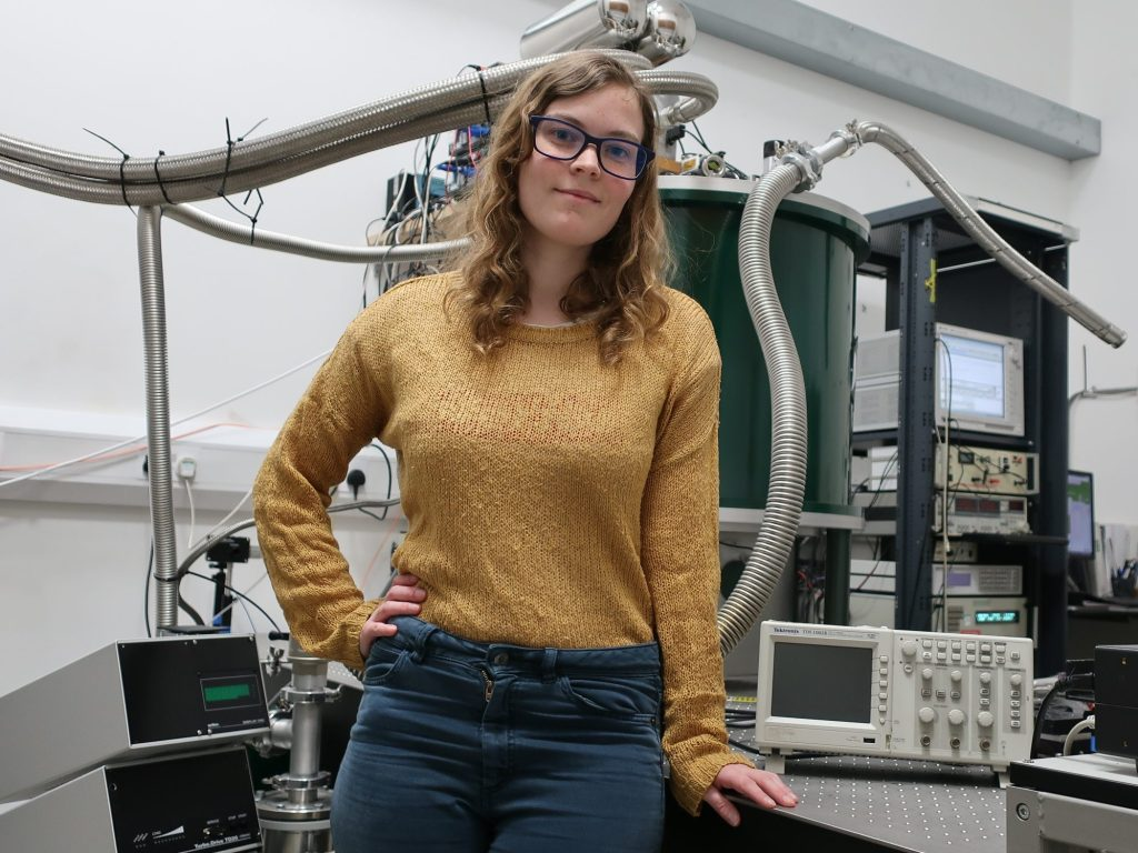 A photo of Daisy Shearer, an experimental quantum physics researcher, in the physics laboratory. She is weating a yellow jumper and various laboratory equipment can be seen in the background.