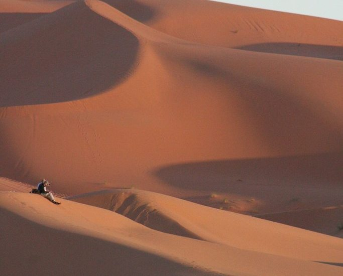 Couple in the sunset at Chebbi Erg dunes at the beginning of the Sahara desert, Morocco (2011-10)