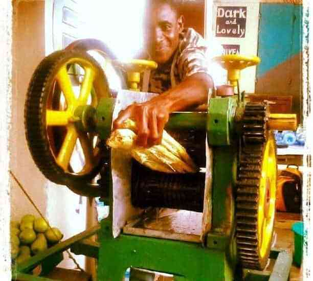 Man making sugar cane juice with a big machine, Mombasa, Kenya (2012-05)