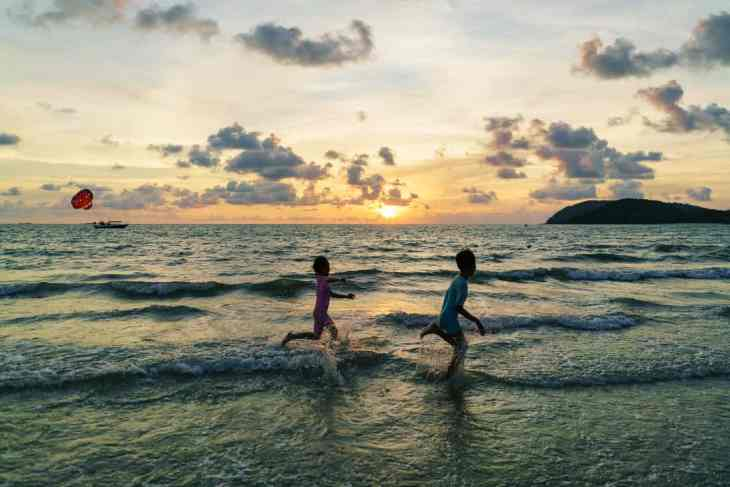 Kids playing at sunset on Pantai Cenang beach, Langkawi, Malaysia