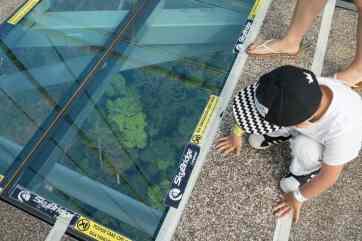 Boy looking through glass floor at SkyBridge, Langkawi, Malaysia