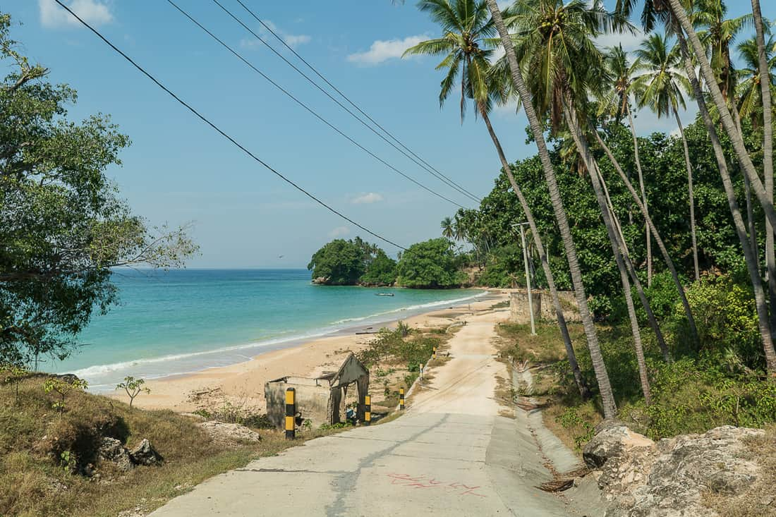 Road along Baucau beach with old toll building, East Timor