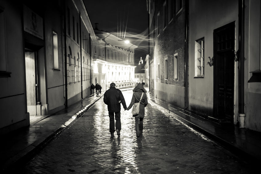 A young couple holding hands walking at night in the old town street,