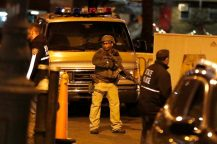 """An armed officer stands guard moments before a motorcade carrying Mexican drug kingpin Joaquin """"El Chapo"""" Guzman arrived at the Metropolitan Correctional Center in New York, Thursday, Jan. 19, 2017. The infamous drug kingpin who twice escaped from maximum-security prisons in Mexico was extradited at the request of the U.S. to face drug trafficking and other charges, and landed in New York late Thursday, a federal law enforcement official said. (AP Photo/Julio Cortez)"""
