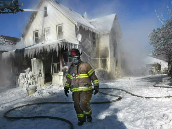 A firefighter walks past an ice-encrusted home after an early morning house fire Wednesday, Jan. 30, 2019 in St. Paul, Minn. Firefighters were called to the house fire in the North End shortly after 4:15 a.m. The air temperature was 27 degrees below zero Wednesday morning, with windchills at 52 degrees below zero. No injuries were reported. (Jean Pieri/Pioneer Press via AP)