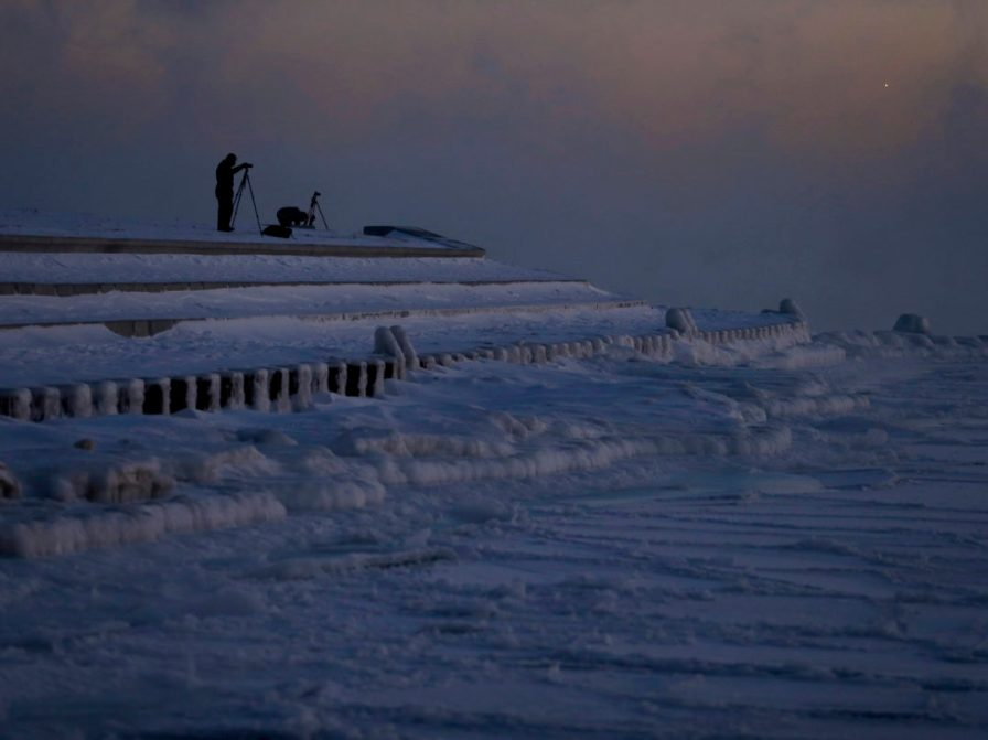 Photographers set up tripods along the shore of Lake Michigan before sunrise, Thursday, Jan. 31, 2019, in Chicago. The painfully cold weather system that put much of the Midwest into a historic deep freeze was expected to ease Thursday, though temperatures still tumbled to record lows in some places. (AP Photo/Kiichiro Sato)
