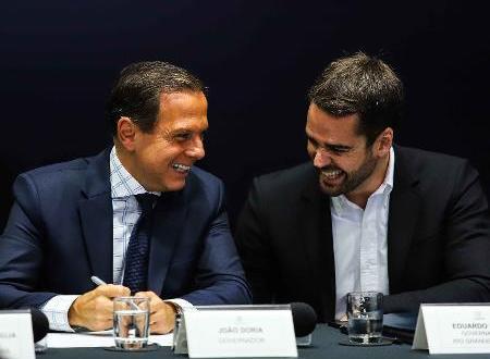Doria e Edurado Leite usam ternos e estão em uma coletiva de imprensa. Eles sorriem.