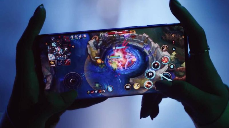 Hands holding a cell phone with Wild Rift game to illustrate story from China