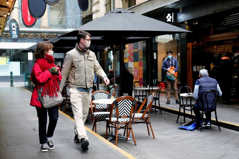 FILE PHOTO: People walk past a cafe after the coronavirus disease (COVID-19) restrictions were eased for the state of Victoria, in Melbourne, Australia, October 28, 2020. REUTERS/Sandra Sanders