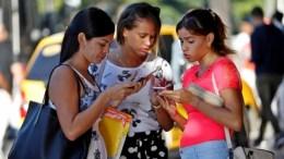 Jóvenes cubanas revisan su móvil en La Habana