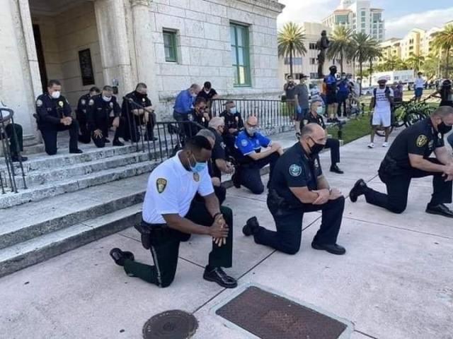 Policías se arrodillan a orar frente a los manifestantes