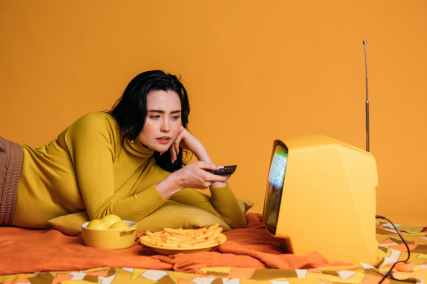 woman in yellow long sleeve shirt watching tv in bed