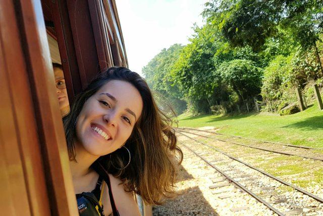 A jornalista Carol Rodrigues, com a cabeça para fora da janela da Maria Fumaça, cabelos ao vento