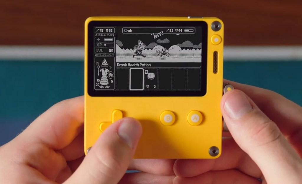La computadora de mano Playdate con una persona jugando en ella.