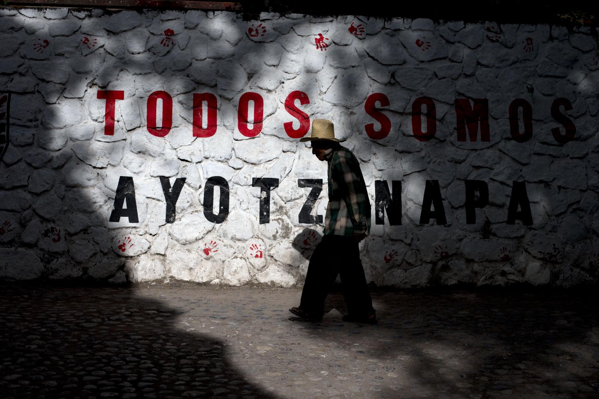 """Un año después de la desaparición, un hombre pasa junto a un muro donde se lee """"Todos somos Ayotzinapa""""."""