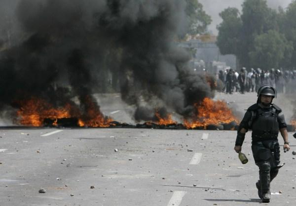 Un policía anti motín del Estado de México pasa junto a una barricada en el enfrentamiento de Atenco en el año 2006.