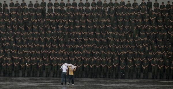 Dos personas caminan hacia un grupo de soldados en una ceremonia militar el día 14 de septiembre de 2009.