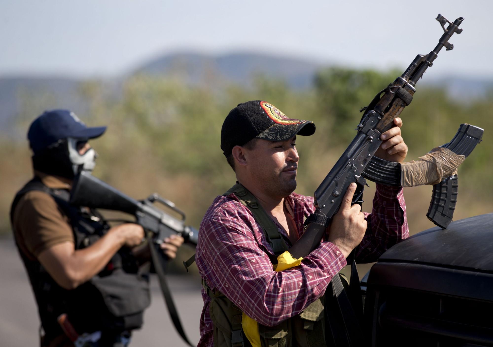 Miembros de las Autodefensas de Michoacán hacen guardia en un punto de control.