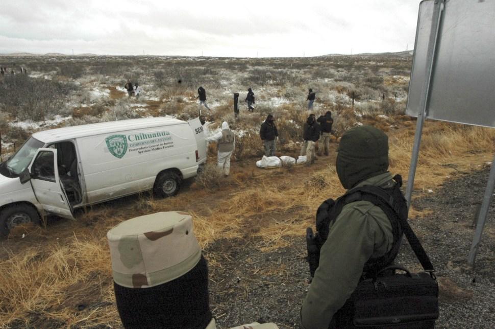 Soldados ven mientras la policía y los investigadores forenses suben cuerpos a camionetas. Esto es en las afueras de Ciudad Juárez, después de que hombres armados abrieran fuego contra seis personas.