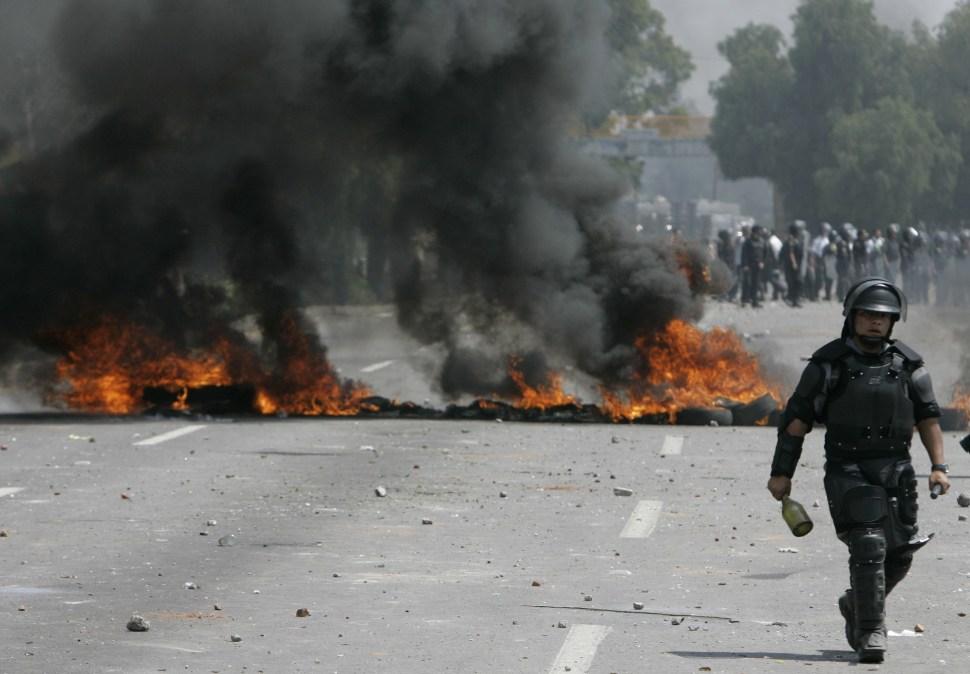 Un policía anti motín del Estado de México pasa junto a una barricada durante el enfrentamiento de Atenco en el año 2006.