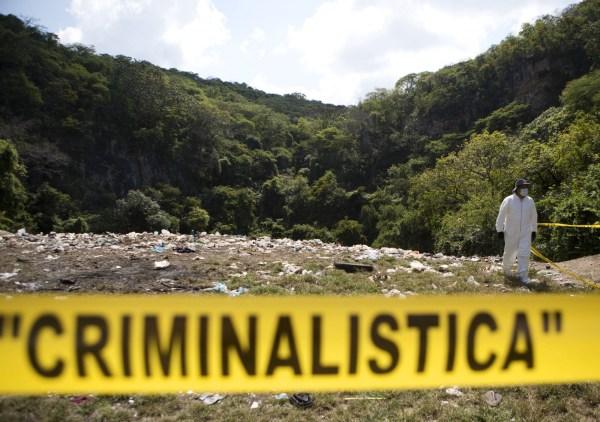 Un examinador forense camina en el basurero de Cocula para investigar sobre los presuntos restos de los 43 desaparecidos.