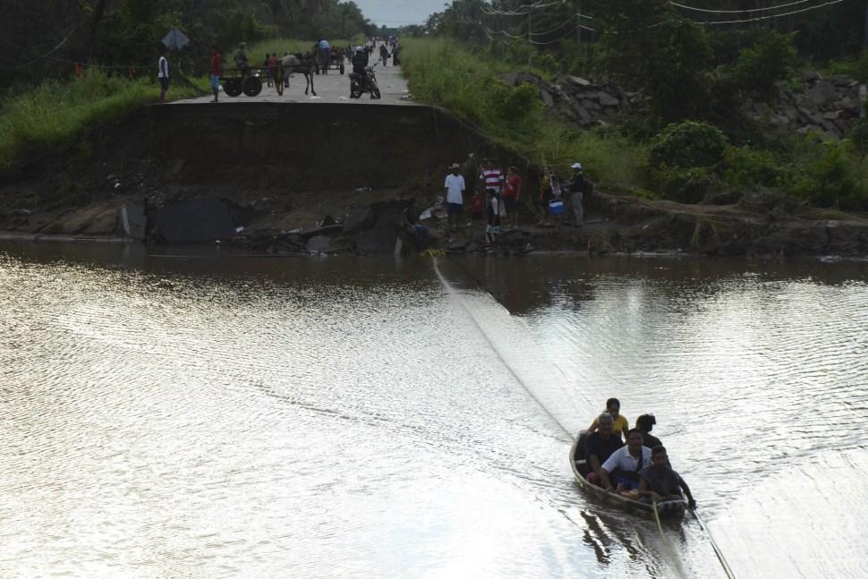 Gente cruza en un bote después de que se colapsara un puente en las cercanías de Atoyac. Esto fue provocado por los huracanes Ingrid y Manuel, que llevaron a la muerte a cientos de personas.