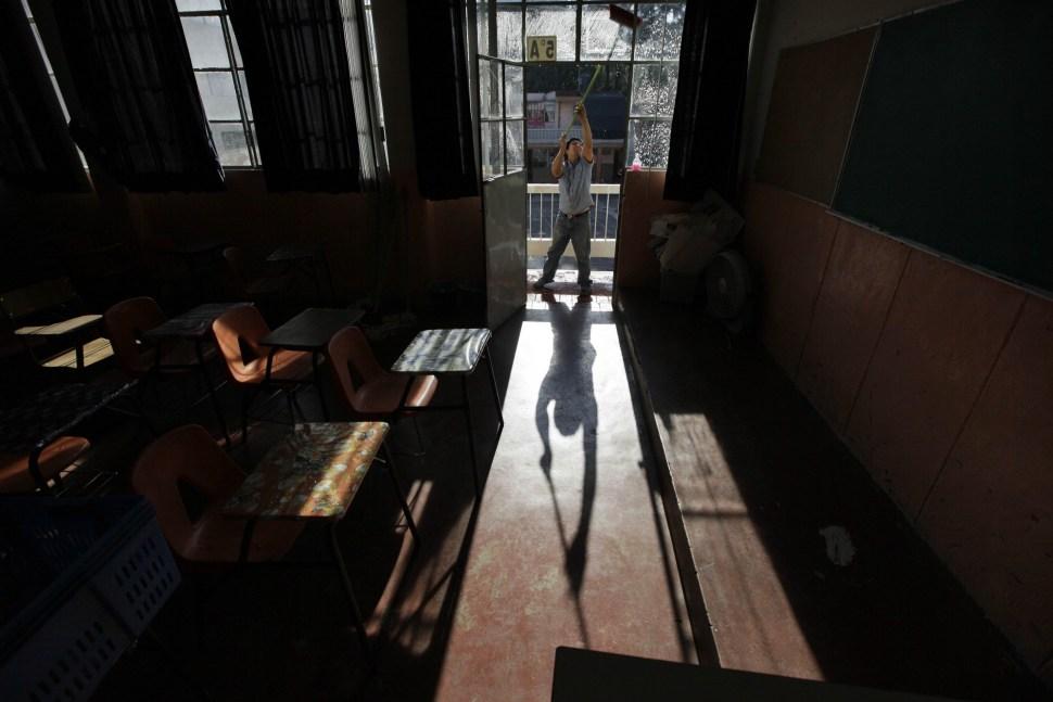 Un voluntario limpia las ventanas de una escuela primaria mientras esta cierra como precaución para evitar contagios de influenza entre los niños.