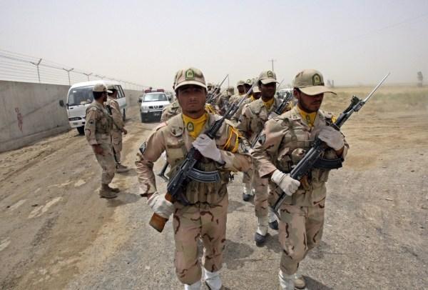 Guardias fronterizos iraníes marchan junto al muro que separa Irán y Pakistán.