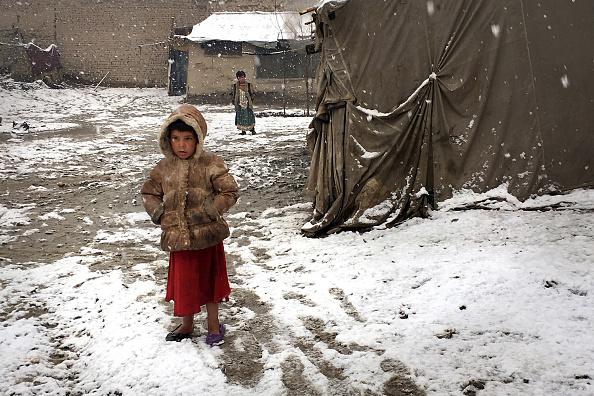 Un niño se encuentra parado afuera de la choza de barro donde vive su familia en Kabul. (Getty Images)