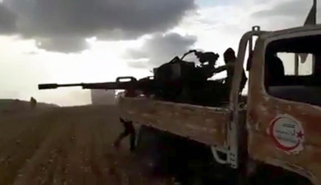 Combatientes de la oposición siria, respaldados por Turquía, disparan sus armas durante unos enfrentamientos con tropas sirias y activistas progubernamentales, cerca del norte de Siria De al-Bab, provincia de Alepo, Siria. (AP)