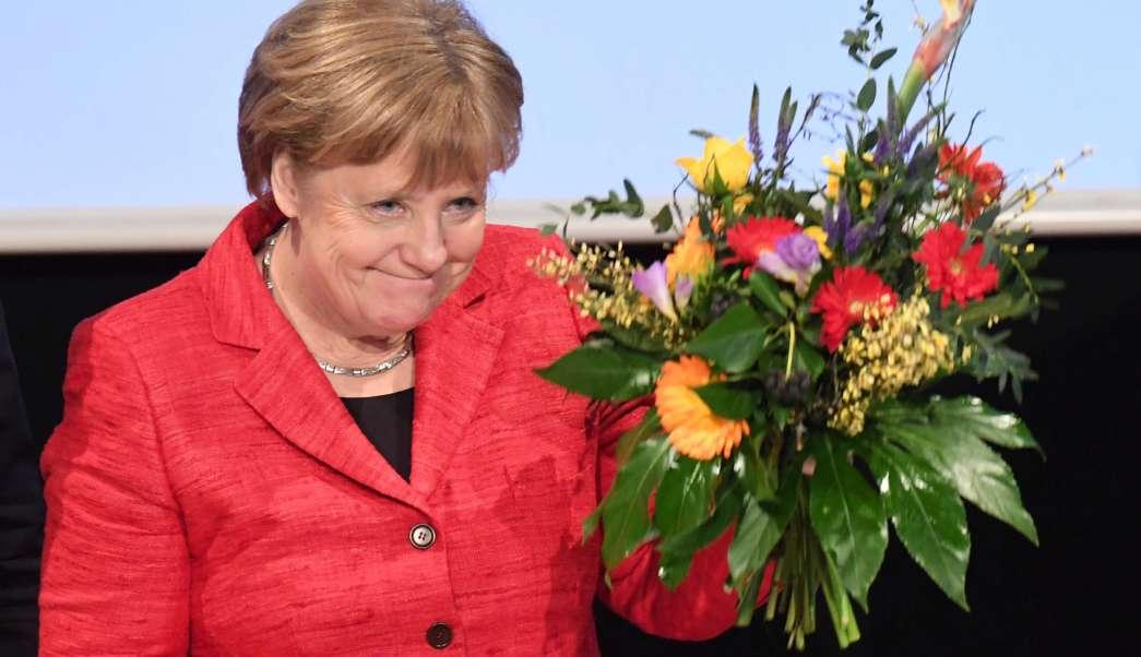 La canciller alemana Angela Merkel sostiene un manojo de flores en una convención de los Demócratas Cristianos en el estado de Mecklemburgo-Pomerania Occidental en Stralsund, Alemania. (AP)