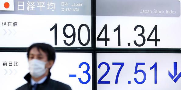 Un hombre camina frente a una pantalla que muestra el resultado de la sesión en la Bolsa de Tokio. (Getty Images)