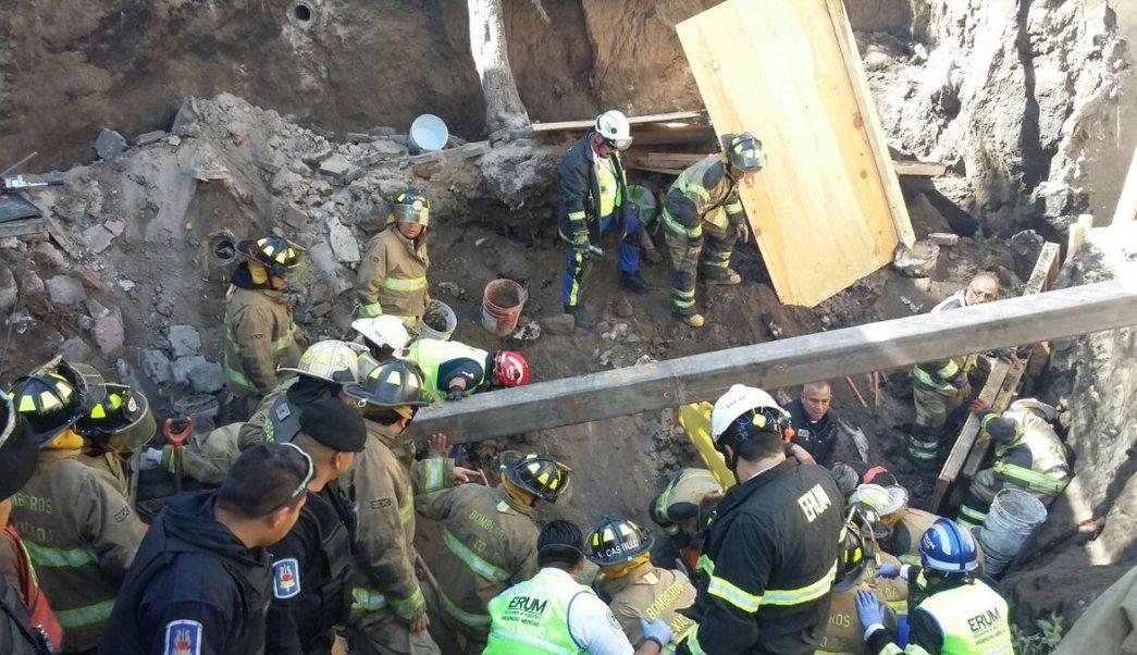 Bomberos trabajan en el rescate de las personas atrapadas por la caída de una barda. (Twitter/@FaustoLugo)