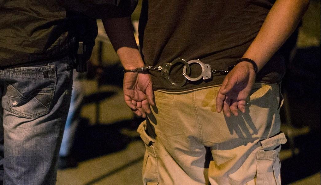 Persona detenida escoltado con esposas; en Monterrey un individuo fue detenido tras un cateo a un comercio donde se almacenaba ropa de marca sin registro de autenticidad