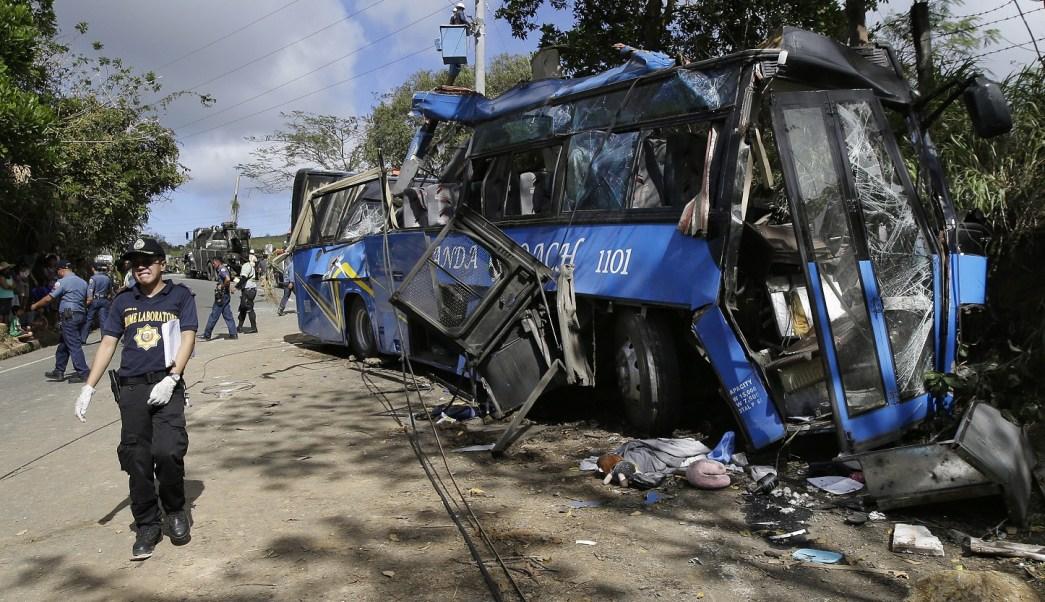 Un investigador de la policía pasa por los restos de un autobús con estudiantes que se estrelló en una carretera al este de Manila, Filipinas (AP)