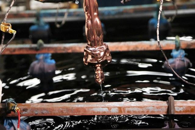 Una estatuilla del Oscar es bañada en químicos durante el proceso de fundición en el barrio de Brooklyn, Nueva York (AP)
