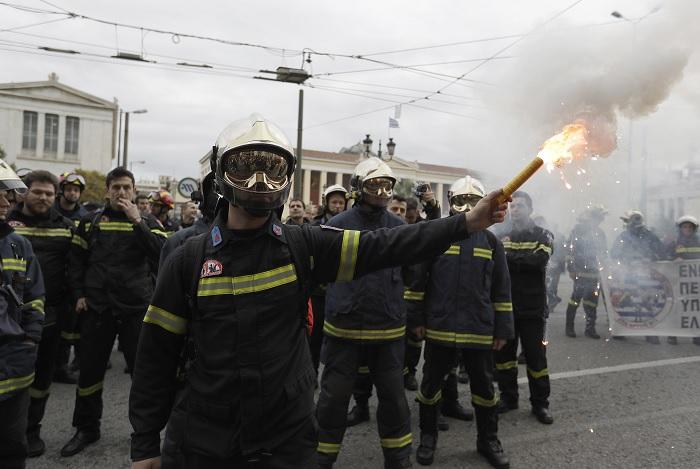 Un bombero sostiene una luz de bengala durante una protesta en el centro de Atenas (AP)