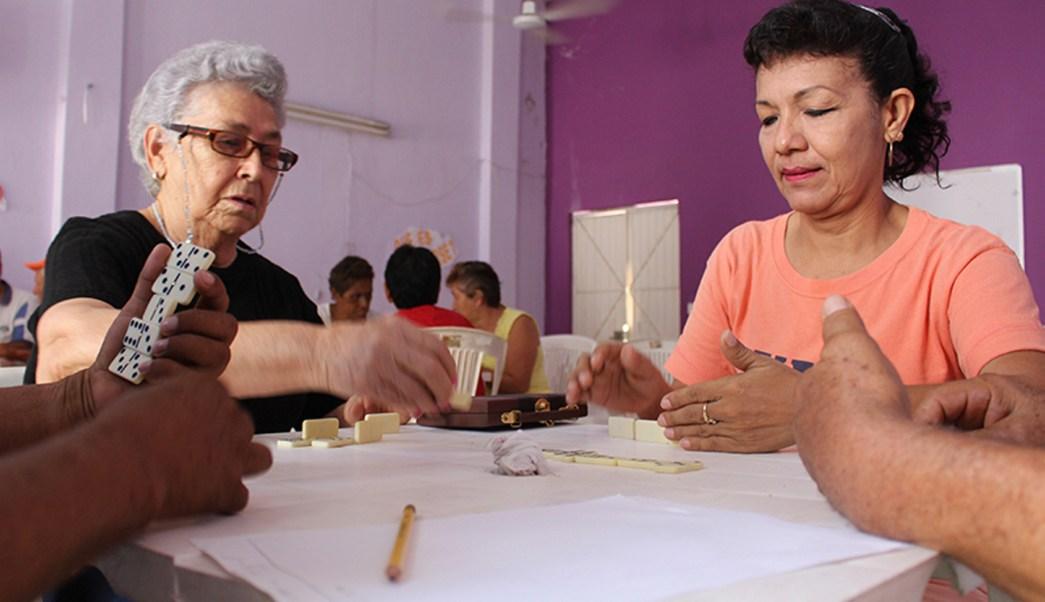 Personas disfrutan de una partida de dominó; los juegos mentales y el ejercicio retrasan la aparición de Alzheimer, afirma neuróloga