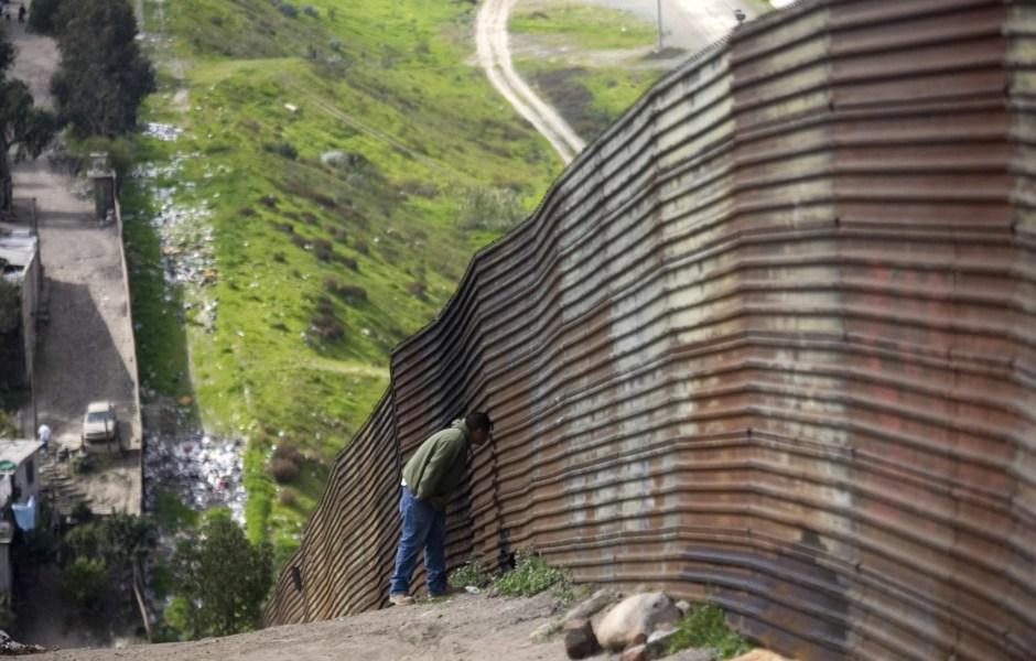 Un hombre se asoma en la frontera de México