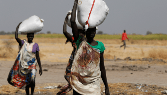 Mujeres en Sudán del Sur cargando sacos de alimento; la ONU advierte de hambruna en ese país. (Reuters, archivo)