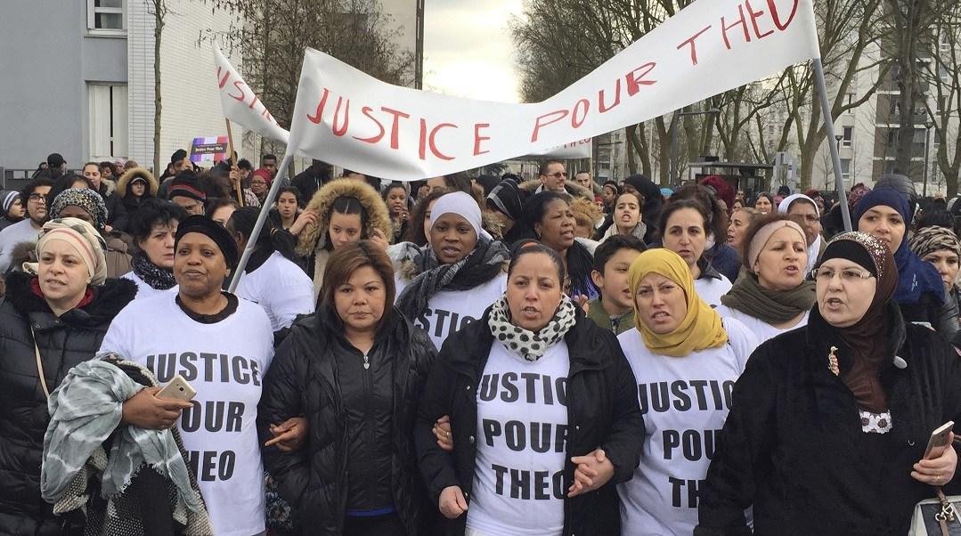 """La gente marcha en las calles de Aulnay-sous-Bois, al norte de París, Francia, con un cartel que dice """"Justicia para Theo"""" durante una protesta (AP)"""