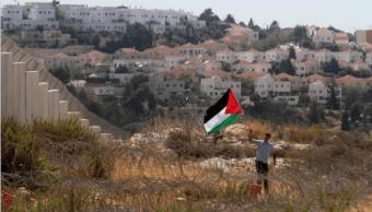 Un activista palestino protesta cerca de asentamientos israelíes.