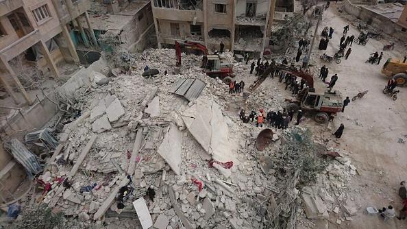 Un grupo de rescatistas con máquinas de excavación inician la búsqueda de cuerpos bajo los escombros después de que los Warcrafts llevaron a cabo ataques aéreos en el distrito de Kusur de Idlib, Siria. (Getty Images)