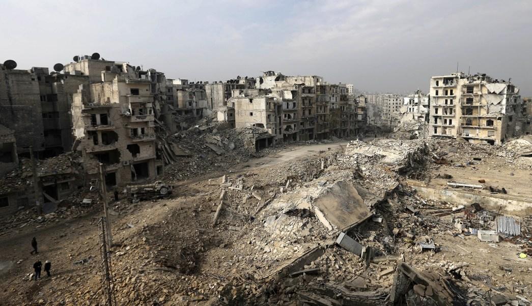 La gente camina a través de montones de escombros que solían ser edificios de apartamentos altos en el vecindario Ansari, este de Alepo, Siria (AP)