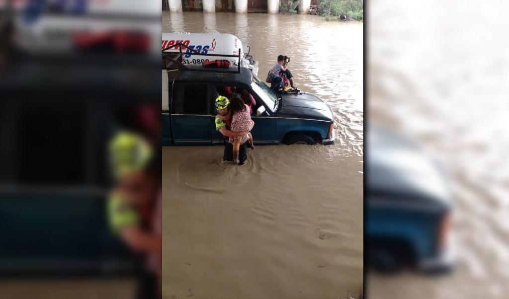 Rescatista auxilia a varias personas que quedaron varadas en el arroyo San Martín, municipio de García (Twitter @_LASNOTICIASMTY)